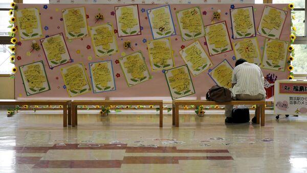 Турист сидит на станции Фукусима напротив доски с посланиями поддержки от жителей префектуры Тиба - Sputnik Italia