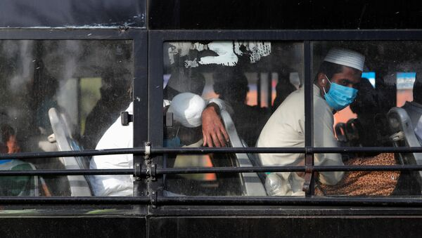 Men wearing protective masks sit inside a bus that will take them to a quarantine facility, amid concerns about the spread of coronavirus disease (COVID-19), in Nizamuddin area of New Delhi, India, March 31, 2020 - Sputnik Italia