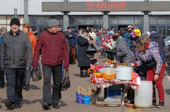Donne vendono ortaggi e fiori artificiali in bancarelle illegali di fronte alla fabbrica di trattori mentre le persone tornano a casa dopo il loro turno a Minsk, Bielorussia, il 31 marzo 2020 - Sputnik Italia