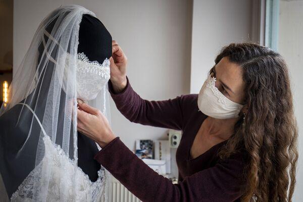 Una stilista finalizza un abito da sposa con una mascherina protettiva in un negozio a Berlino, Germania - Sputnik Italia