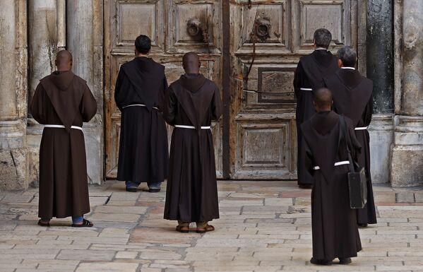 Frati francescani durante la preghiera davanti alla porta chiusa della basilica del Santo Sepolcro, Gerusalemme - Sputnik Italia