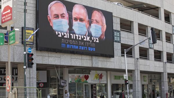A billboard shows Israeli Prime Minister Benjamin Netanyahu, left, Israeli Former Defense Minister and leader of the Yisrael Beiteinu (Israel Our Home) right-wing party Avigdor Lieberman, center, and Blue and White party leader Benny Gantz, wearing masks in the Israeli city of Ramat Gan, near Tel Aviv, Sunday, March 29, 2020.  - Sputnik Italia