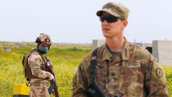 Un soldato iracheno indossa maschera e guanti dopo l'esplosione dell'epidemia da coronavirus(COVID-19) Mosul, Iraq Marzo 26, 2020. - Sputnik Italia