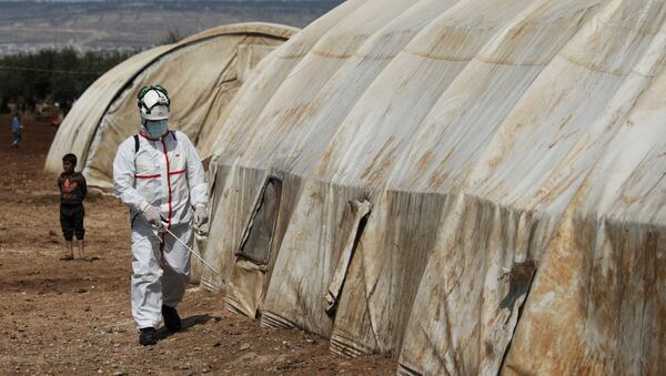 A member of the Syrian Civil defence sanitizes a tent at the Bab Al-Nour internally displaced persons camp, to prevent the spread of coronavirus disease (COVID-19) in Azaz, Syria 26 March 2020. - Sputnik Italia