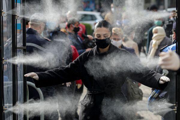 Le persone vengono disinfettate prima di entrare in un mercato, poiché le autorità albanesi hanno adottato le misure per fermare la diffusione del coronavirus (COVID-19) a Tirana, Albania, il 6 aprile 2020 - Sputnik Italia