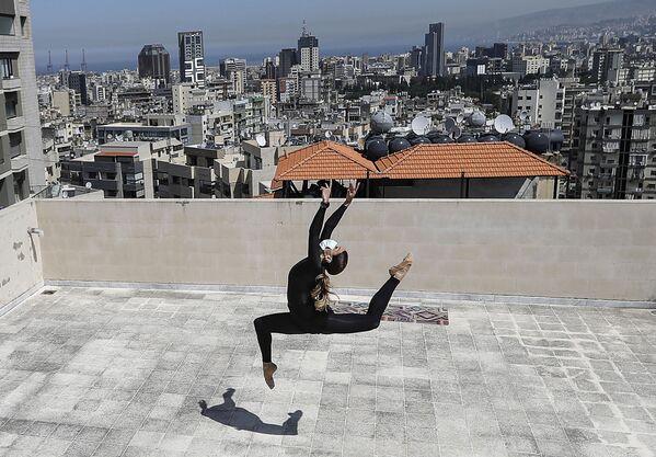 Sherazade Mami, una ballerina tunisina di 28 anni, performer al teatro di danza Caracalla e l'insegnante alla scuola di danza Caracalla, si esercita sul tetto del suo condominio nel sobborgo di Dekwaneh alla periferia orientale della capitale del Libano, Beirut, il 4 aprile 2020 - Sputnik Italia