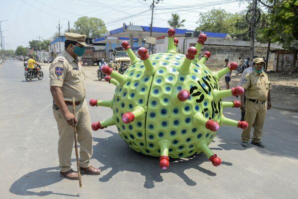 Gli agenti di polizia pattugliano le strade mentre l'inventore Sudhakar Yadav (all'interno) guida la sua auto a forma della cellula del coronavirus durante il lockdown imposto dal governo come misura preventiva contro il coronavirus a Hyderabad, l'8 aprile 2020 - Sputnik Italia
