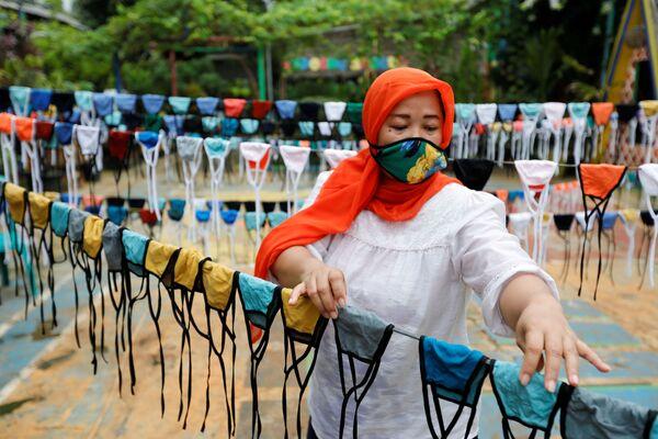 Una donna mette le maschere di stoffa su una corda per asciugarle prima di distribuirle gratuitamente nel quartiere a Tangerang, nella periferia di Jakarta, Indonesia, il 9 aprile 2020 - Sputnik Italia