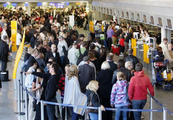 I passeggeri fanno la coda all'aeroporto di Francoforte, Germania. L'aeroporto è stato chiuso a causa della cenere vulcanica negli strati alti dell'atmosfera sopra l'Europa. Costituendo una minaccia per i motori degli aerei, la presenza di cenere ha portato alla cancellazione di molti voli nello spazio aereo europeo. - Sputnik Italia