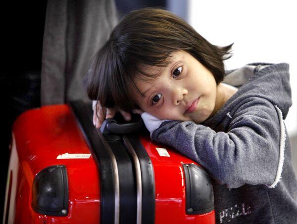 Una bambina riposa sulle valigie all'aeroporto di Francoforte, Germania. L'aeroporto è stato chiuso a causa della cenere vulcanica negli strati alti dell'atmosfera sopra l'Europa. Visto che il cenere costituisce una minaccia per i motori degli aerei, molti voli nello spazio aereo europeo sono stati cancellati. - Sputnik Italia