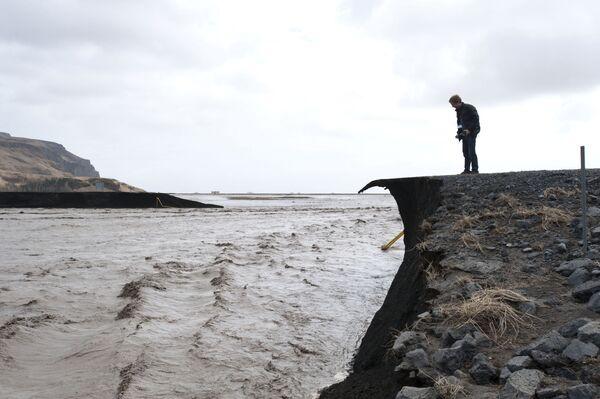 Un uomo sta fotografando la strada che è stata distrutta dall'alluvione dopo lo scioglimento del ghiacciaio Eyjafjallajökull dovuto all'eruzione del vulcano. - Sputnik Italia