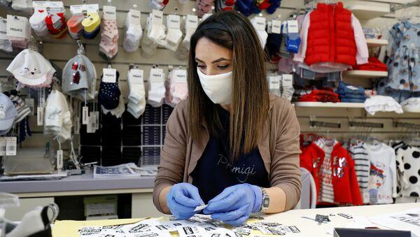 Una donna in mascherina in un negozio per bambini a Catania, Italia - Sputnik Italia