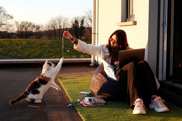 Ragazza gioca con un gatto sulla soglia della sua casa in un villaggio belga - Sputnik Italia