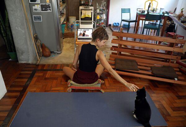 L'istruttrice di yoga Chris Igreja accarezza il suo gatto durante una lezione di yoga online a Rio de Janeiro, Brasile, il 19 marzo 2020 - Sputnik Italia