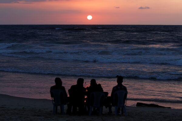 I palestinesi si godono il tramonto su una spiaggia nella Striscia di Gaza, il 10 aprile 2020 - Sputnik Italia