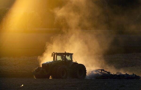 Un trattore in un campo al tramonto a Minsk, Bielorussia - Sputnik Italia