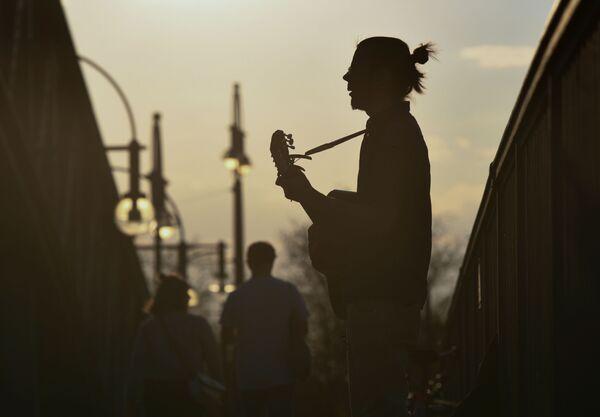 Un uomo suona una chitarra su un ponte al tramonto a Berlino, Germania, il 12 aprile 2020 - Sputnik Italia