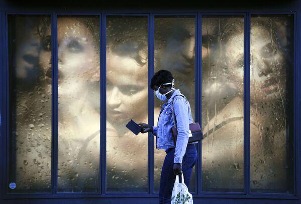 Una donna che indossa una maschera protettiva passa davanti alla vetrina di un negozio a Parigi, il 14 aprile 2020 - Sputnik Italia