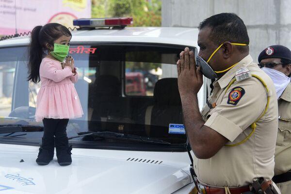 La donna più piccola del mondo, Jyoti Amge, saluta un ufficiale di polizia a Nagpure, il 13 Aprile 2020 - Sputnik Italia