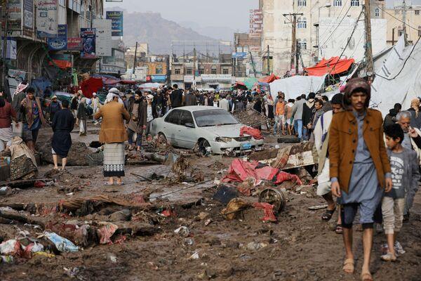 La gente cammina su una strada danneggiata in una zona allagata da forti piogge a Sanaa, Yemen, il 14 aprile 2020 - Sputnik Italia