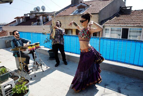 La ballerina Su Sevda Uzun si esibisce dalla terrazza della casa per i suoi vicini accompagnata dai musicisti Hakan Kaya e Alper Kalayciklioglu a Istanbul, Turchia, il 13 aprile il 2020 - Sputnik Italia