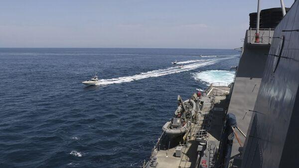 Una motovedetta della Guardia Rivoluzionaria naviga in prossimità di una nave militare della Marina USA nel Golfo Persico, nei pressi del Quwait, 15 aprile 2020 - Sputnik Italia
