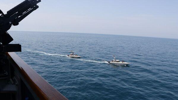 Due motovedette della Guardia Rivoluzionaria naviga in prossimità di una nave militare della Marina USA nel Golfo Persico, 15 aprile 2020 - Sputnik Italia