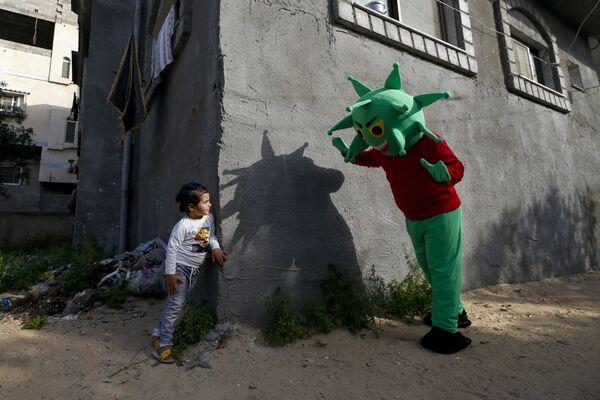 Un uomo palestinese che indossa un costume di coronavirus gioca con una bambina nella Striscia di Gaza, il 20 aprile 2020 - Sputnik Italia