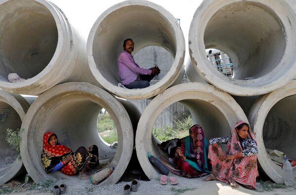 Migranti riposano in tubi di cemento durante un blocco a livello nazionale per rallentare la diffusione della malattia da coronavirus a Lucknow, India, il 22 aprile 2020 - Sputnik Italia