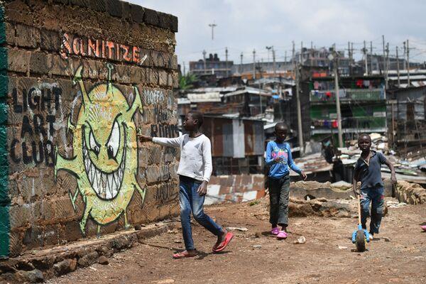 Un ragazzo legge il messaggio informativo murale che avverte le persone del rischio del coronavirus COVID-19 a Nairobi, in Kenya, il 22 aprile 2020 - Sputnik Italia