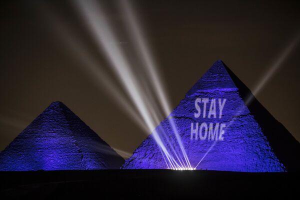 Una proiezione laser con il messaggio Resta a casa sulle Grandi piramidi di Giza, Egitto, il 18 aprile 2020  - Sputnik Italia