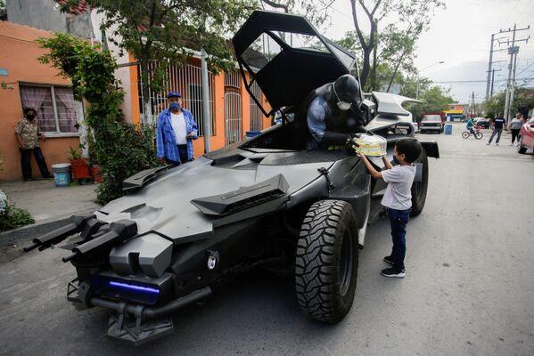 L'avvocato messicano Candelario Maldonado, vestito come da Batman, regala una torta di compleanno a un bambino che indossa una maschera di fronte a casa sua, durante la pandemia edl coronavirus (COVID-19), a Monterrey, Messico, il 18 aprile 2020 - Sputnik Italia