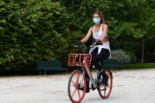 Una donna guida una bicicletta a noleggio attraverso a Milano dopo l'inizio della Fase 2, Italia, il 4 maggio 2020 - Sputnik Italia