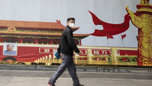 A resident wearing a mask against coronavirus walks past government propaganda poster featuring Tiananmen Gate in Wuhan in central China's Hubei province Thursday, April 16, 2020 - Sputnik Italia