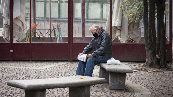 Un uomo legge un giornale in una via di Torino - Sputnik Italia