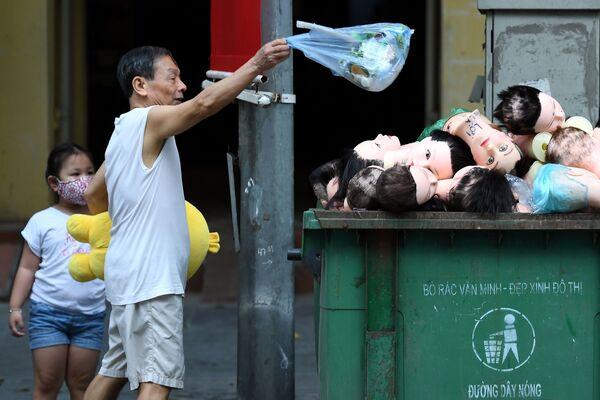 Un uomo getta l'immondizia nel cassonetto con le teste dei manichini a Hanoi, Vietnam. - Sputnik Italia
