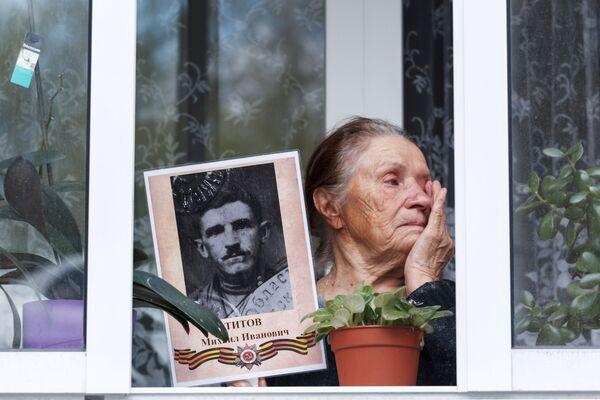 Un'abitante di Irkutsk con la foto di un suo parente, veterano della Seconda Guerra Mondiale. - Sputnik Italia