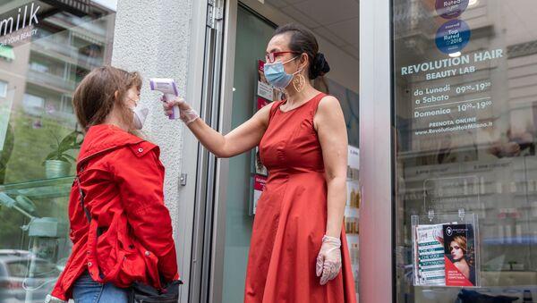 Una dipendente di un parrucchiere misura la temperatura a una cliente a Milano - Sputnik Italia