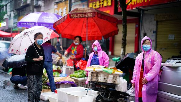 Le persone che indossano maschere protettive vengono viste in un mercato di strada a Wuhan, la città cinese più colpita dall'epidemia di coronavirus (COVID-19), nella provincia di Hubei, Cina, 14 maggio 2020. - Sputnik Italia