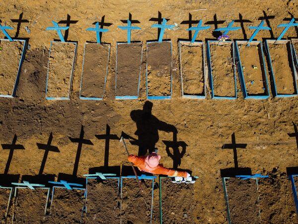 Un becchino al cimitero Nossa Senhora Aparecida dove vengono sepolte le vittime del Covid-19 nei pressi della città di Taruma, Brasile. - Sputnik Italia