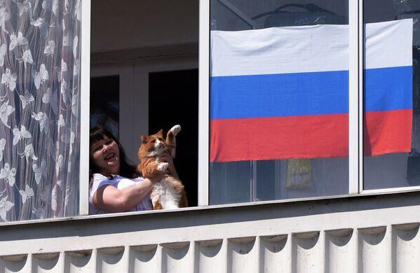 Una residente di Krasnoyarsk guarda il concerto della banda musicale in occasione del Giorno della Russia dalla finestra del suo appartamento - Sputnik Italia
