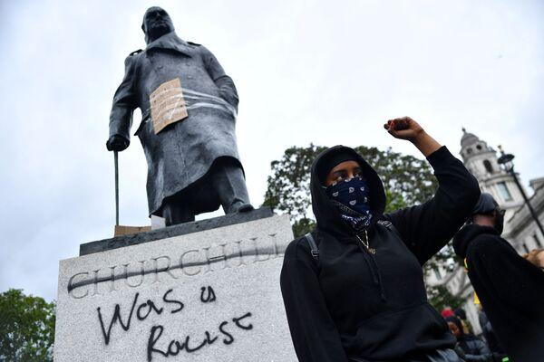Un manifestante davanti ai graffiti su una statua di Winston Churchill durante una protesta di Black Lives Matter a Londra, il 7 giugno 2020 - Sputnik Italia