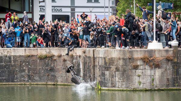 La statua del commerciante di schiavi del 17° secolo Edward Colston cade in acqua dopo che i manifestanti l'hanno abbattuta durante una protesta contro la disuguaglianza razziale a seguito della morte di George Floyd a Minneapolis, Bristol, Gran Bretagna, il 7 giugno 2020 - Sputnik Italia