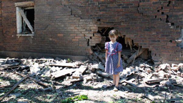 Una ragazzina davanti alla casa distrutta dai bombardamenti dell'esercito ucraino a Gorlovka, Donbass. - Sputnik Italia